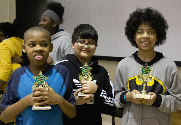 Three O'Neal boys each hold a 'Hidden Figure' trophy