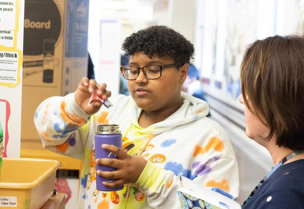 Student scientist pours liquid into a bottle