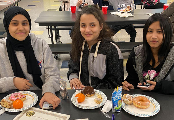 Three girls sit at a table eating breakfast