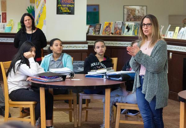 Three students listen to author Ann Burg speaks