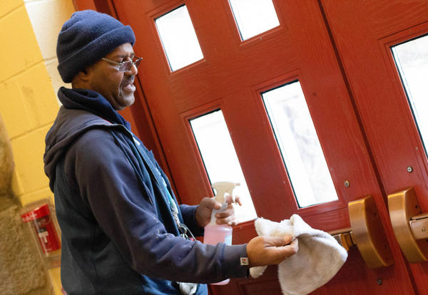 Maintenance worker cleans a door handle with disinfectant and a cloth