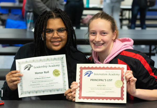 Two young women hold up the certificates they earned for Honor Roll and Principal's List