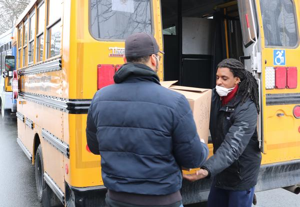 Two district employees loading a box of food onto a yellow school bus