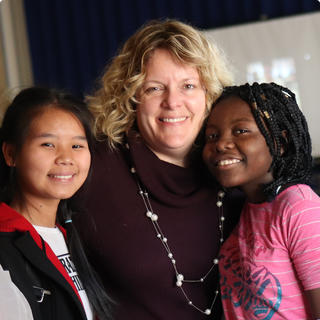 Principal Rachel Stead posing for a photo with two students.