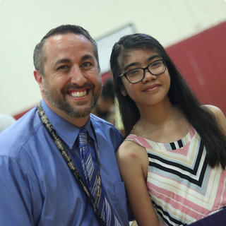 Principal Gabe Barbato posing for a photo with a student.