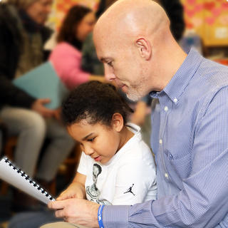 Principal John Powell reading with a student