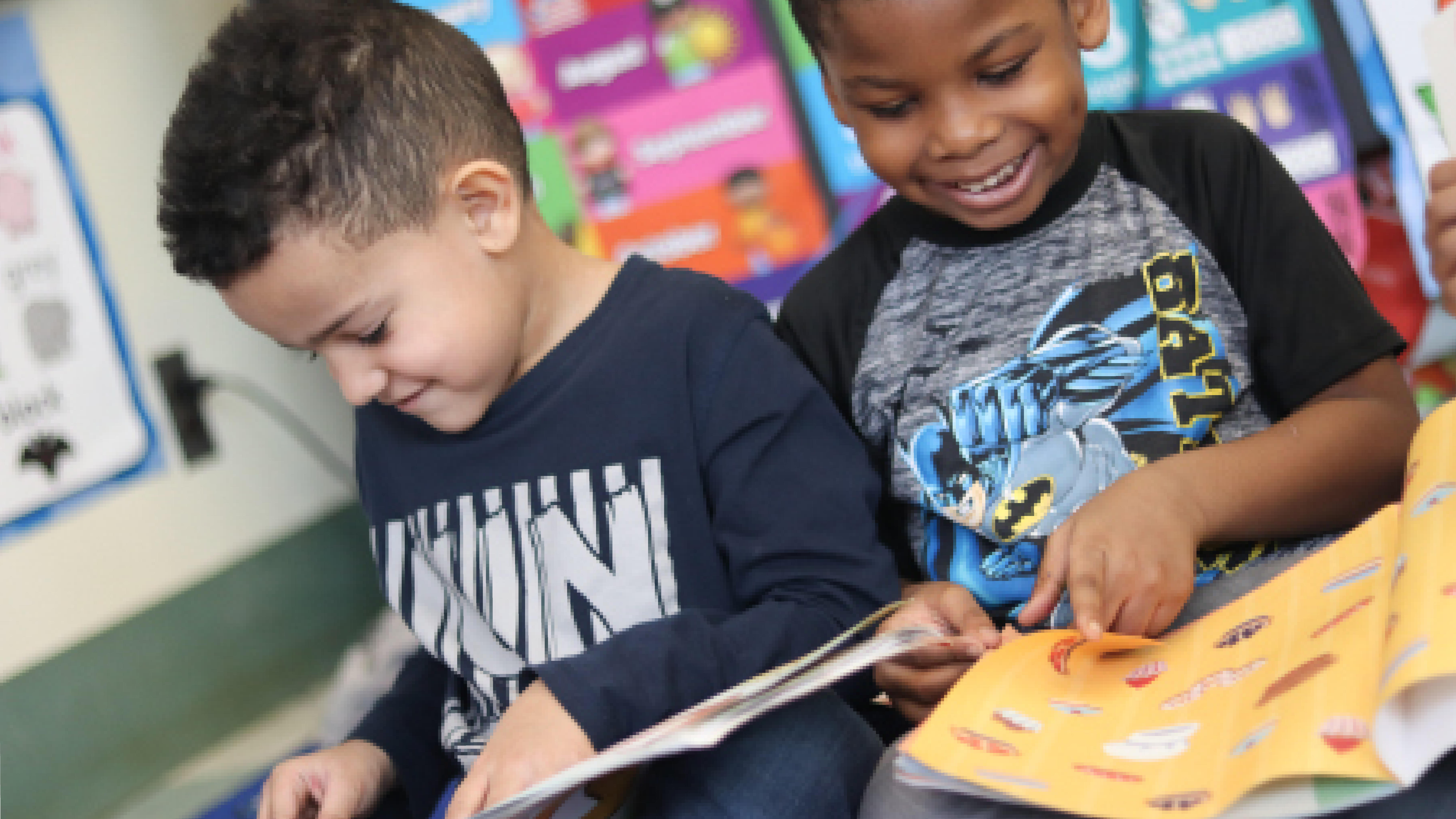 Two prekindergarten boys happily reading books on the carpet.