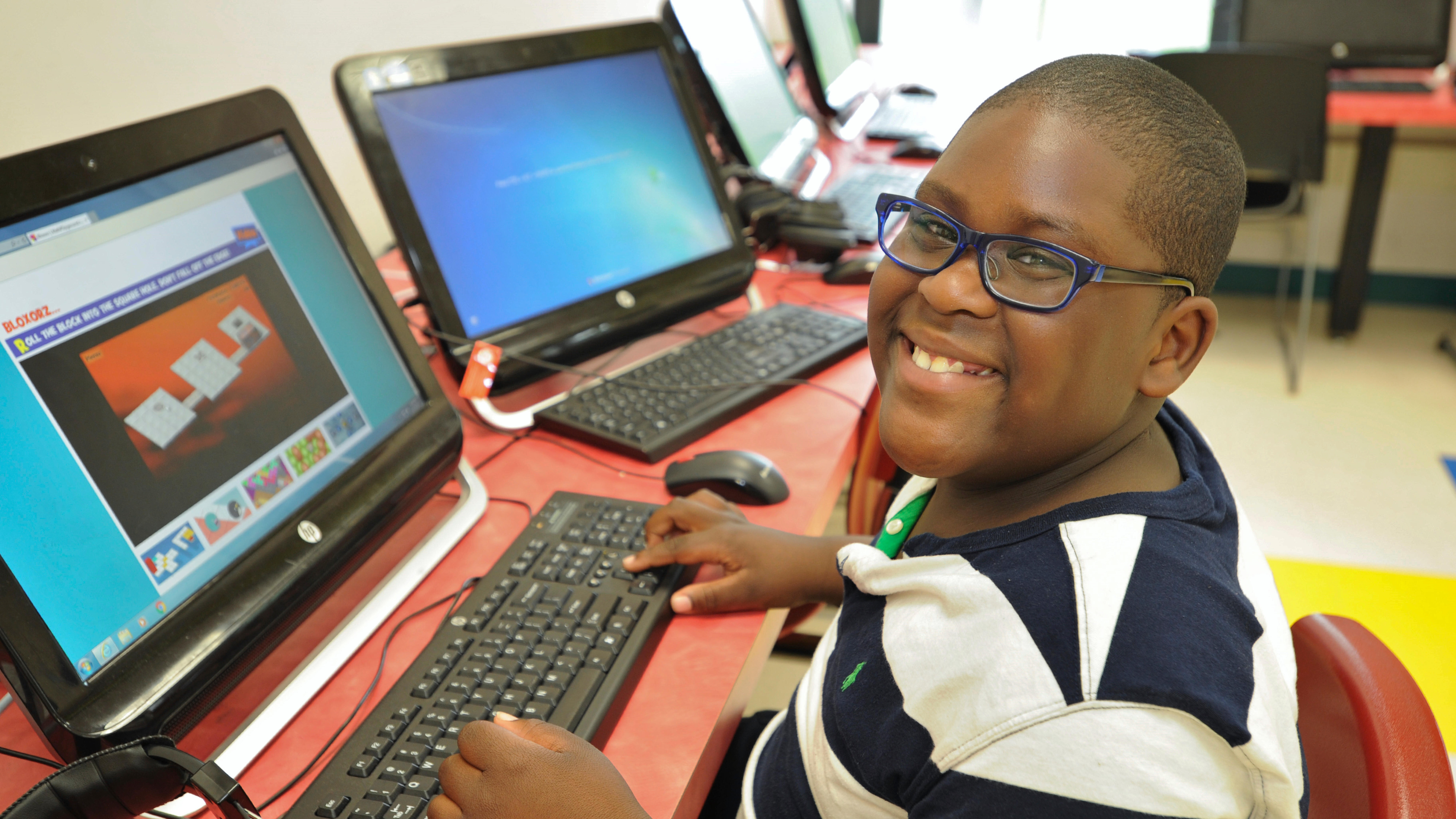 Special Education student smiling while working at a computer.