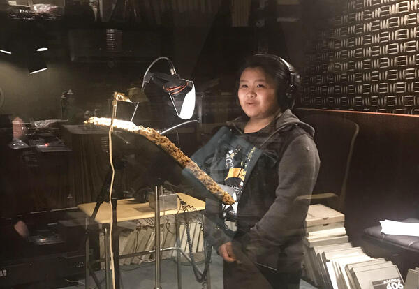 Boy sings at a microphone in a recording studio