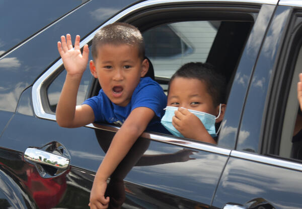 Two boys wave from a car window