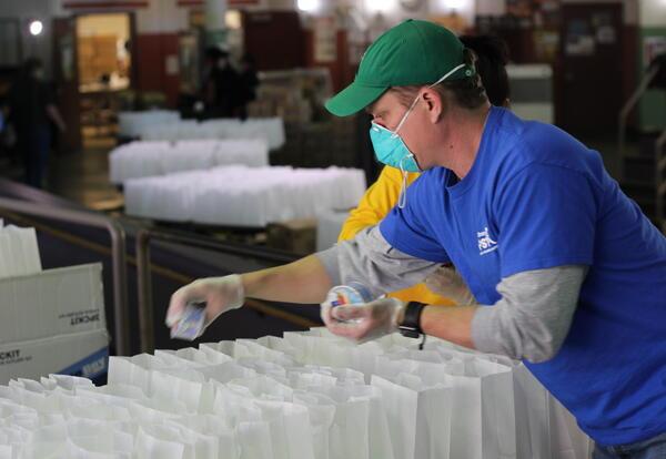 Man packs food in lunch bags
