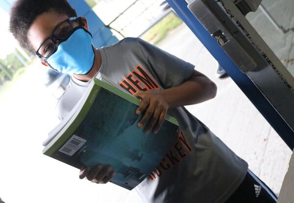 A student at Myers picks up his workbooks.