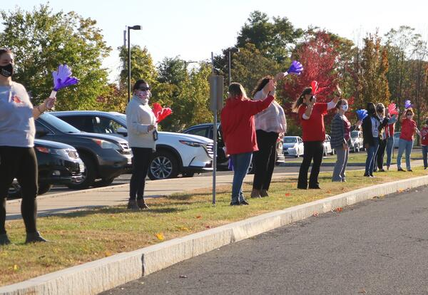 Teachers wave to students in a drive by parade.