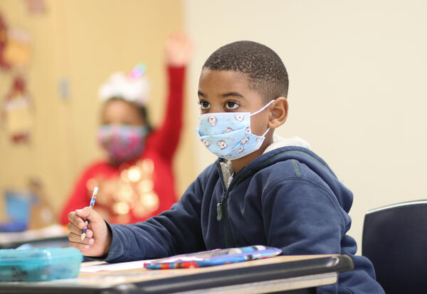 Photo of a male elementary student at his desk with a mask, and a socially distanced female elementary student, also wearing a mask, in the background raising her hand.