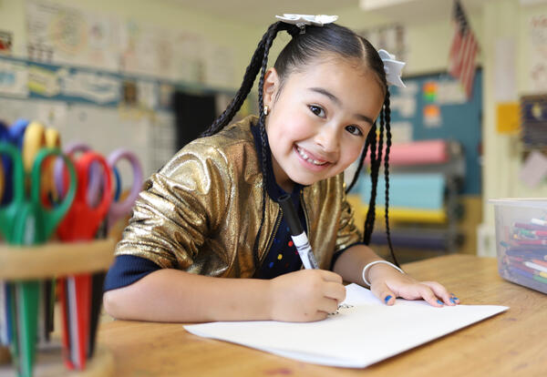 Smiling girl writes on paper with a marker