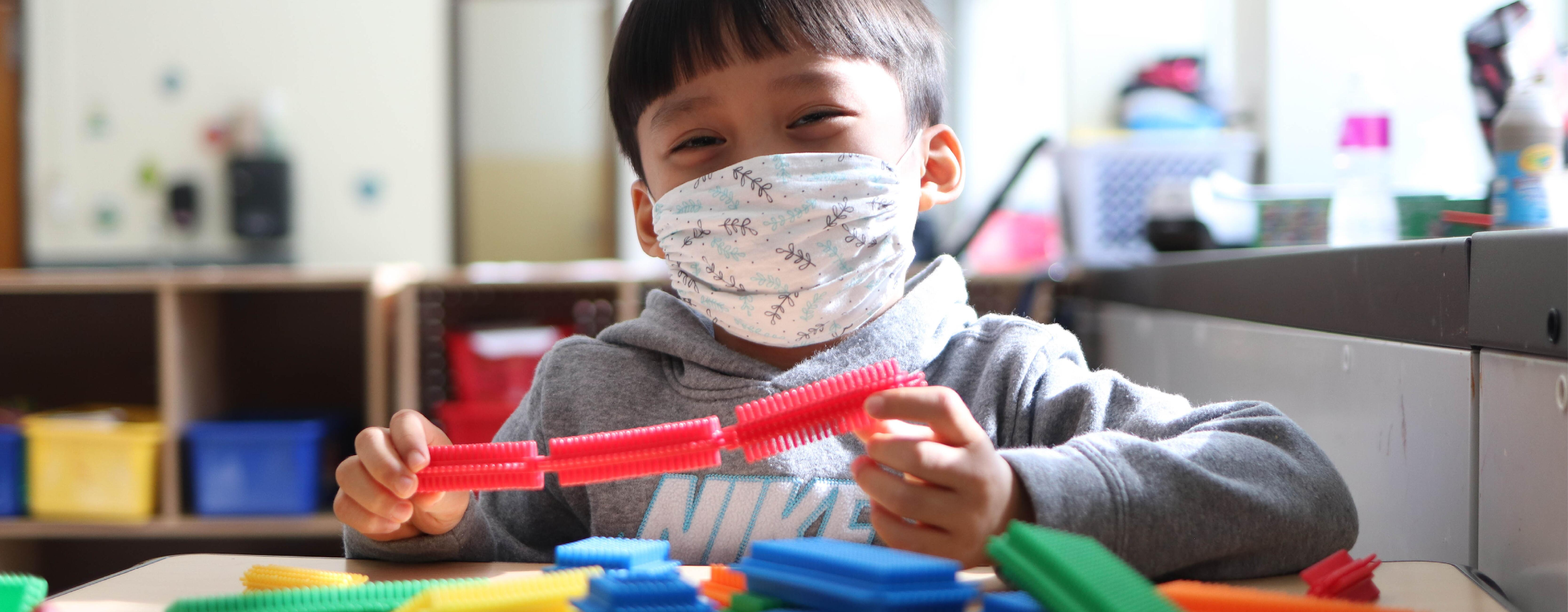 Student wearing a mask and smiling while playing with colorful interlocking blocks.
