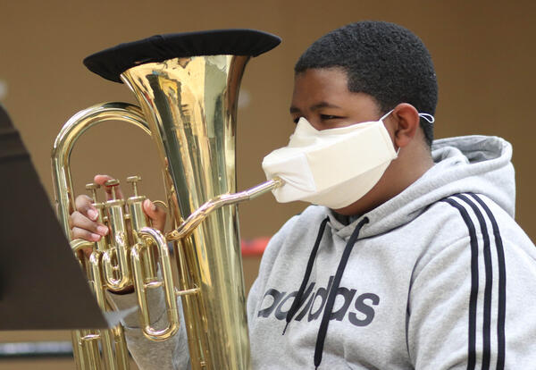 Albany High student wearing COVID-19 mask playing a musical instrument