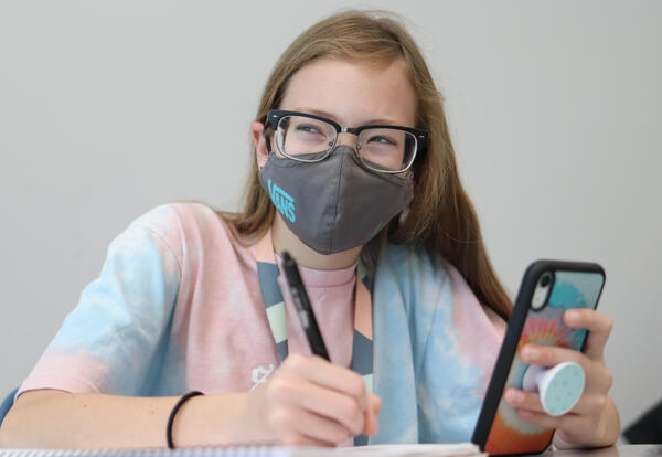 Sixth-grade female student doing schoolwork wearing glasses and a COVID-19 mask in the classroom