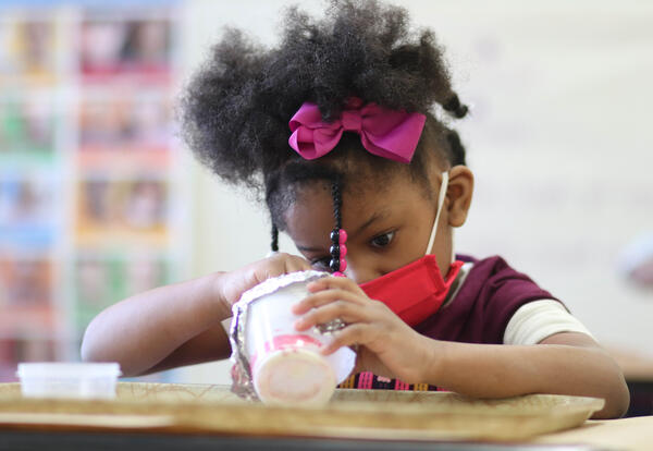 Pre-K student looking into a cup as they mix ingredients inside it
