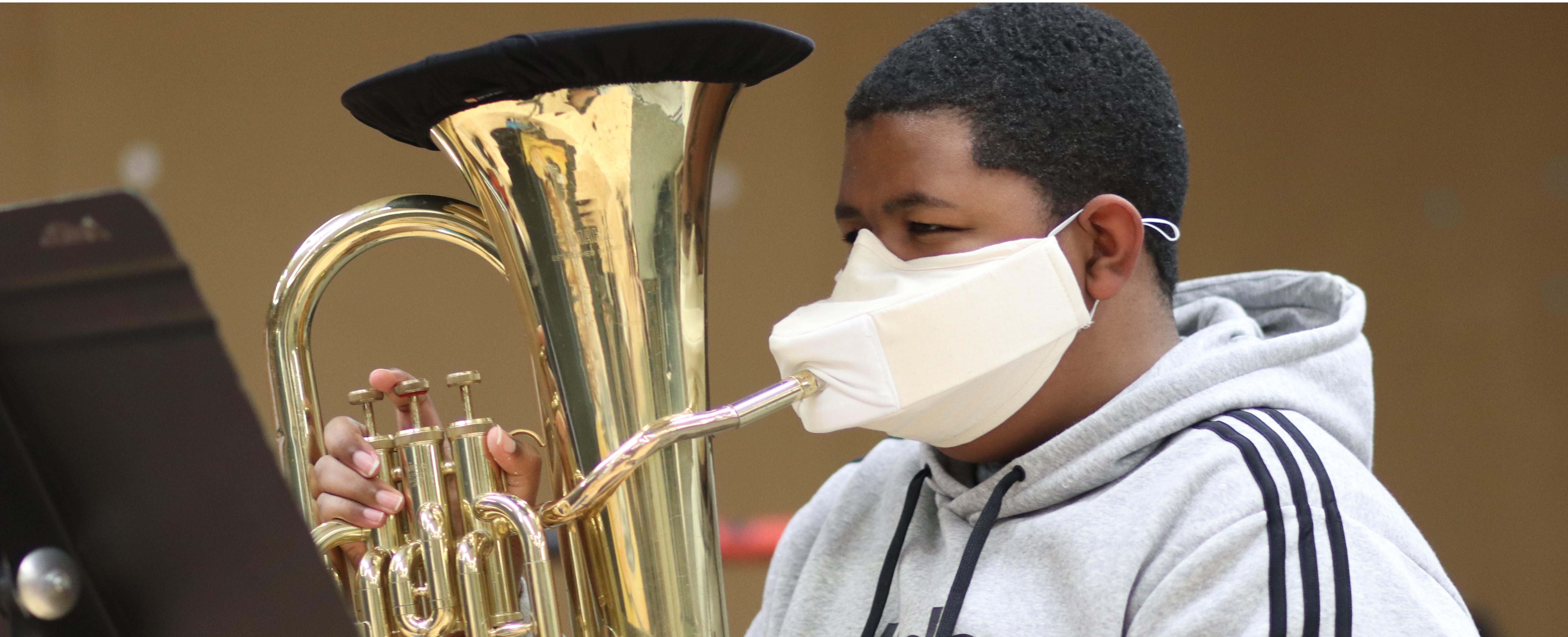 Student wearing a mask holding an instrument.