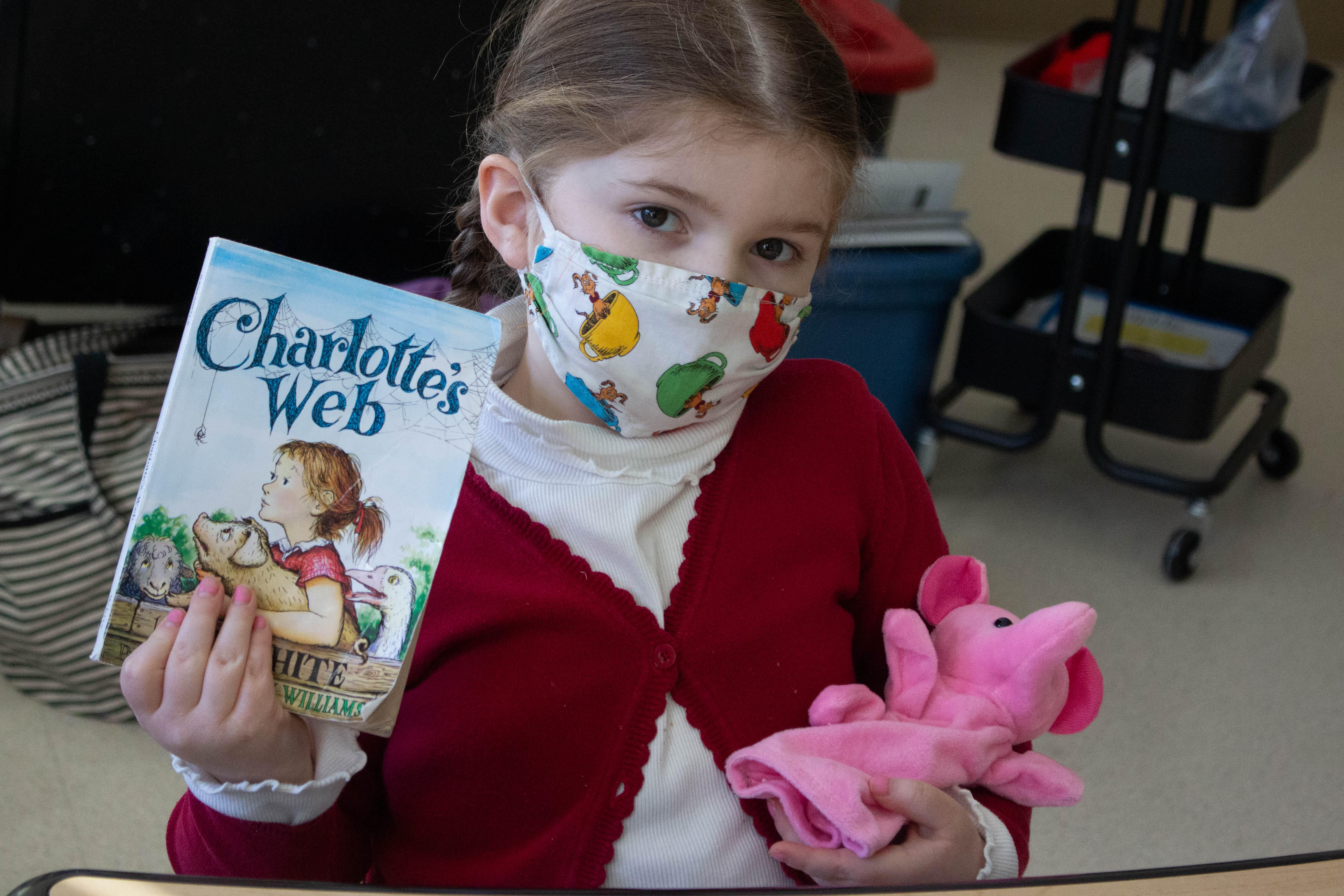 Student posing for a picture holding up a copy of Charlotte's Web and a toy pig