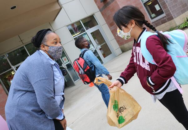 Pine Hills Elementary School Principal Tia Corniel greets a student outside the building's main entrance in September 2020.