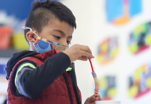 Student threading Froot Loops onto a pipe cleaner to make a rainbow
