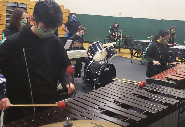 One students plays a marimba and the other plays a drum set.