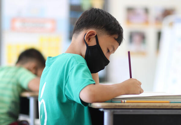 Student working on a writing assignment at their desk