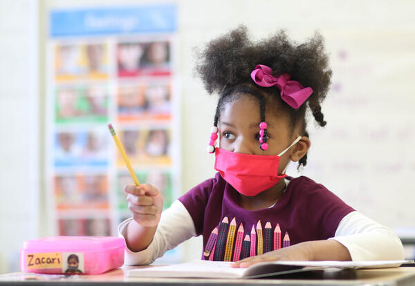 Elementary student with a red COVID-19 facemask and a pink hair bow holding up a pencil to make a point during a classroom lesson.