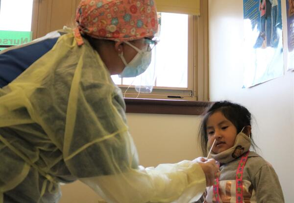 A school nurses tests a student for COVID.