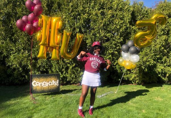 Student wears a Harvard sweatshirt and holds Harvard balloons