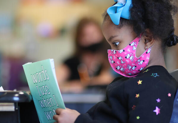 """First-grade student wearing a COVID-19 mask at her desk reading """"Words I Use When I Write."""""""