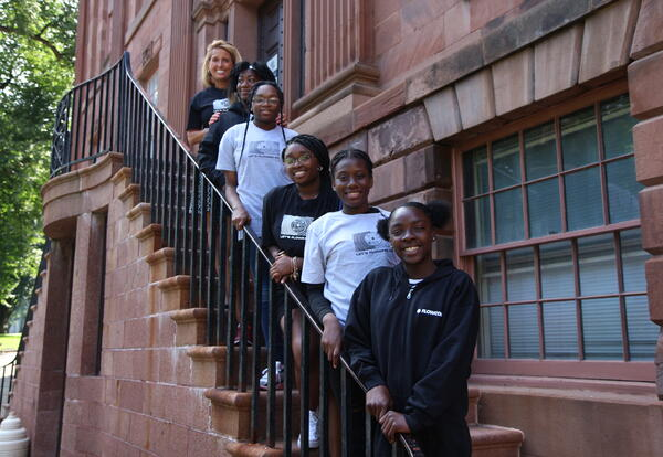 Five students from the VisionVoice program with Assistant Superintendent for Secondary Instruction Lori McKenna standing on the stairs outside Academy Park.
