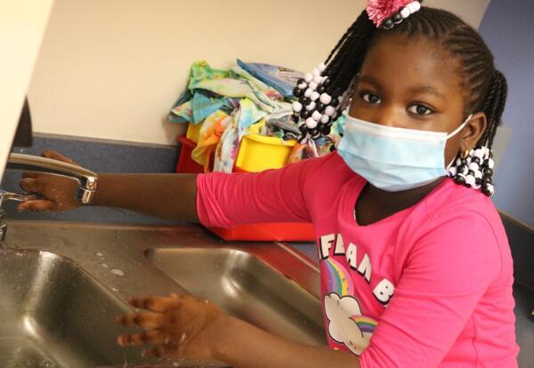 A kindergarten student practices washing her hands.