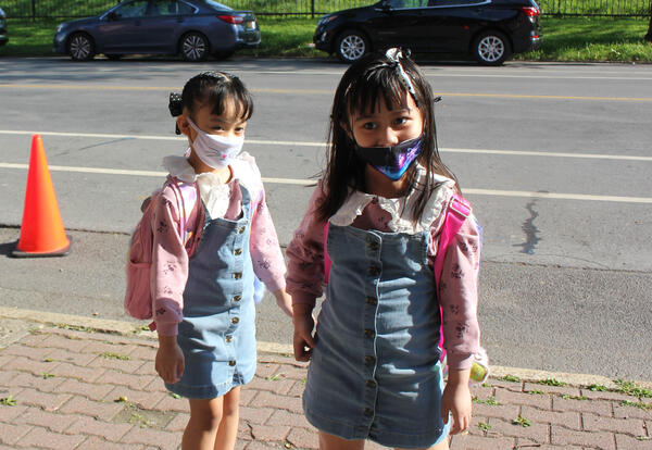 Two little girls in matching denim jumpers walk into school