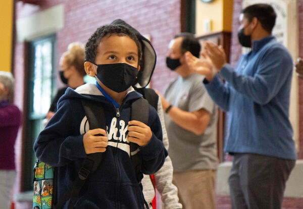 Boy with face mask and backpack walks through line of cheering adults