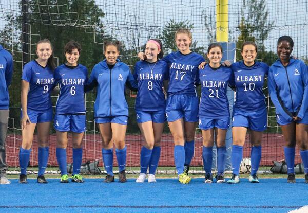 The Albany High girls' soccer team and coaches pose in the goal on Senior Night.
