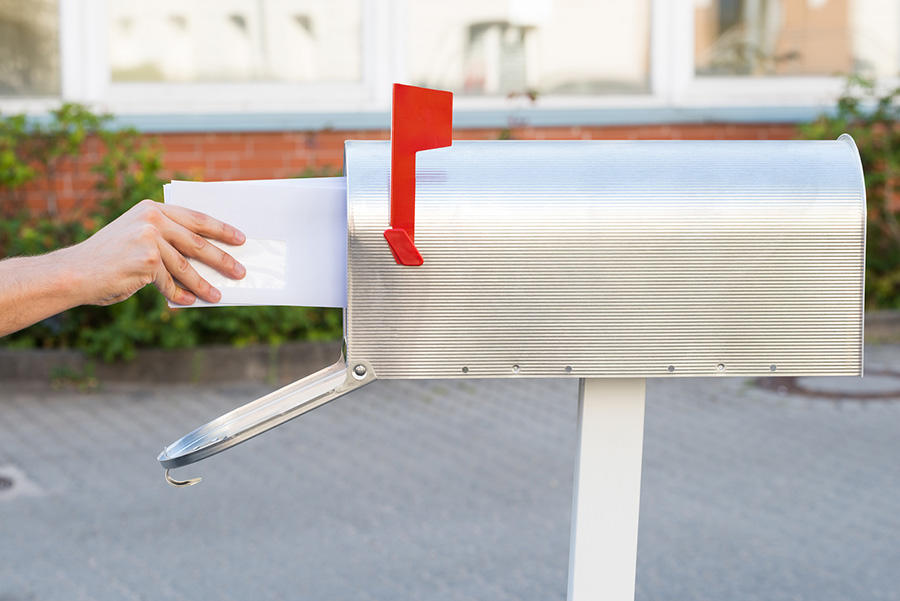 Hand putting letter into the mailbox