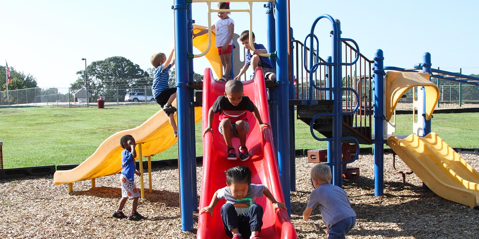 Students going down slide and playing at recess