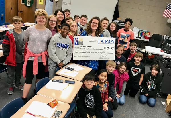 Teachers holding their JacksonEMC Bright Idea grant checks