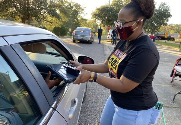 teacher giving out device through car window