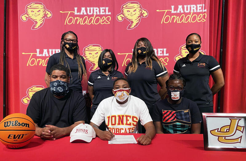 student signs basketball scholarship