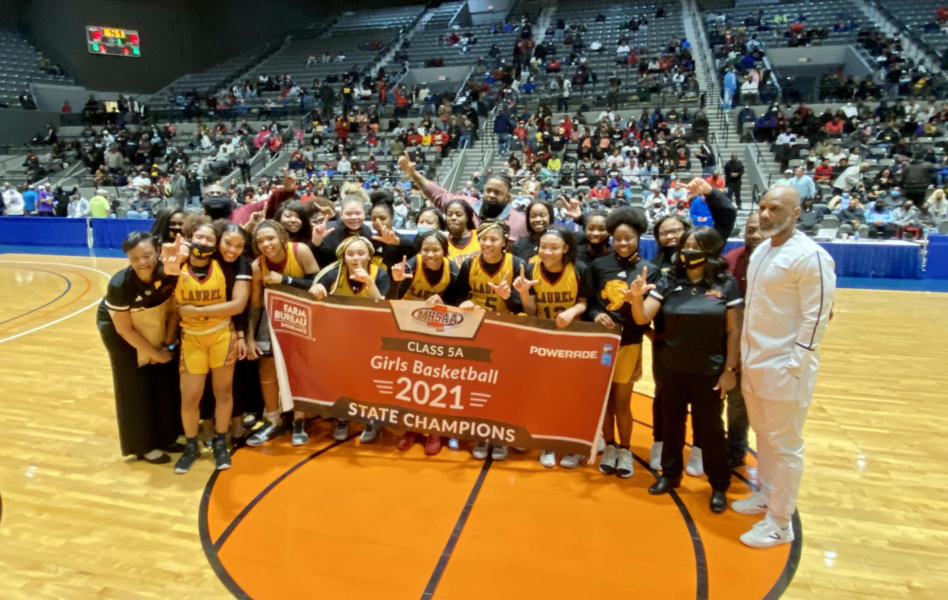 girls basketball team with championship banner