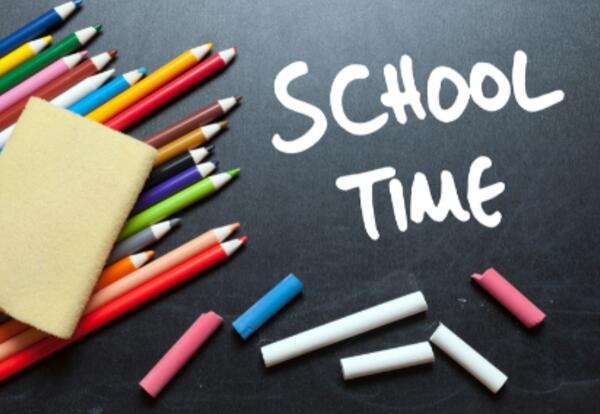 Color pencils and chalk on a blackboard that reads school time.