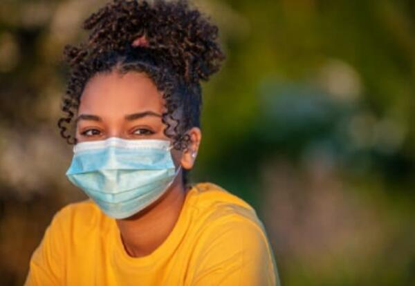 Young teen girl with a face mask on.