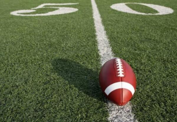 50 Yard line of a football field, with a football centering the line.