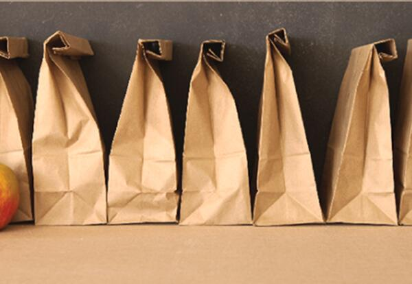 Brown filled paper bags sitting on a table.