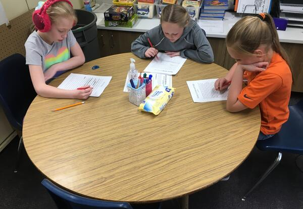 4th-grade students demonstrating communication during writing. They are peer editing each other's work and listening to each other's feedback.