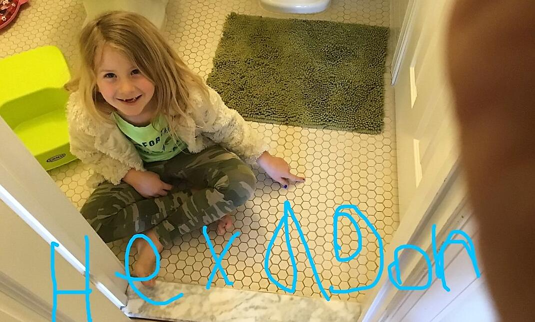 Child pointing to floor tiles